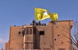 "An image grab released by the Kurdish Ronahi TV on March 23, 2019 shows the US-backed Syrian Democratic Forces (SDF) raising their flag atop a building in the Islamic State group's last bastion in the eastern Syrian village of Baghuz after defeating the jihadist group. - Kurdish-led forces pronounced the death of the Islamic State group's nearly five-year-old ""caliphate"" on March 23, 2019 after flushing out diehard jihadists from their very last bastion in eastern Syria. (Photo by Handout / RONAHI TV / AFP) / XGTY / == RESTRICTED TO EDITORIAL USE - MANDATORY CREDIT ""AFP PHOTO / HO / RONAHI TV"" - NO MARKETING NO ADVERTISING CAMPAIGNS - DISTRIBUTED AS A SERVICE TO CLIENTS =="