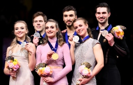 ISU World Figure Skating Championships Ice Dance winner Gabriella Papadakis and Guillaume Cizeron of France (C), silver medalists, Victoria Sinitsina and Nikita Katsalapov of Russia (L) and bronze medalists Madison Hubbell and Zachary Doohue of the US (R) pose with their medals during the victory ceremony in Saitama, northern suburb of Tokyo on March 23, 2019. (Photo by Toshifumi KITAMURA / AFP)