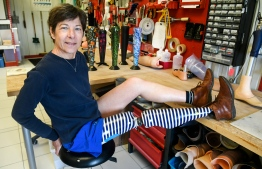 "Evelyne Briand poses with her customized prosthesis at ALGO, a firm specialized in prosthesis in Brest, western France, on March 13, 2019. - ""I did not bear the first prosthesis with foam and a stocking. It was outdated,"" says Evelyne Briand, showing proudly his left leg decorated with navy blue and white stripes. Now decorated, orthopedic appliances are displayed. (Photo by Fred TANNEAU / AFP)"