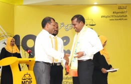 Former President Mohamed Nasheed (L) drapes MDP's 'Agenda 19' sash on Abdul Mughunee, the candidate for the northern constituency of GDh.Thinadhoo. PHOTO/MDP