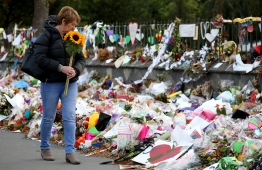 A woman walks past flowers and tributes displayed in memory of the twin mosque massacre victims at the Botanical Garden in Christchurch on March 29, 2019. - The remembrance ceremony is being held in memory of the 50 lives that were lost in the March 15th mosque shootings in Christchurch. (Photo by Sanka VIDANAGAMA / AFP)