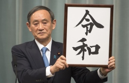 """Japan's Chief Cabinet Secretary Yoshihide Suga announces the new era name """"Reiwa"""" duringa press coference at the prime minister's office in Tokyo on April 1,2019. - Japan announced its new imperial era, which will begin next month when Emperor Akihito abdicates, will be known as """"Reiwa"""", a word that includes the character for """"harmony"""". (Photo by Kazuhiro NOGI / AFP)"""