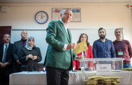 Turkish President Tayyip Erdogan (C) stands prior to cast his ballot at a polling station during the municipal elections in Istanbul, on March 31, 2019. - Turkey voted in local elections  in a test for President Recep Tayyip Erdogan, with his ruling party risking defeat in the capital as an economic slowdown takes hold. (Photo by BULENT KILIC / AFP)
