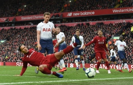 Liverpool's Dutch defender Virgil van Dijk (L) fails to reach the ball during the English Premier League football match between Liverpool and Tottenham Hotspur at Anfield in Liverpool, north west England on March 31, 2019. PHOTO: PAUL ELLIS / AFP