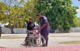 Police aiding an elderly voter at a polling station in Alifushi, Raa Atoll. PHOTO: POLICE TWITTER