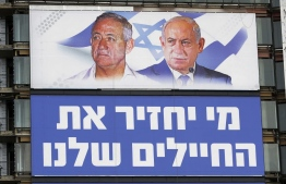 """An electoral billboard for Israel's upcoming general elections bear the portraits of retired general Benny Gantz (L), one of the leaders of the Blue and White (Kahol Lavan) political alliance, and Prime Minister Benjamin Netanyahu(R) from the Likud party is displaced in the Israeli coastal city of Tel Aviv on March 29, 2019. The Hebrew writings read """"Who will bring back our soldiers?"""" (Photo by JACK GUEZ / AFP)"""