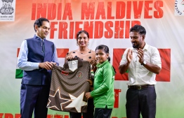 Indian Ambassador to Maldives Sunjay Sundhir and Minister of Education Dr Aishath Ali handing over sports attire to students. PHOTO: MIHAARU