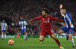 Liverpool's Egyptian midfielder Mohamed Salah (C) vies with Porto's Brazilian midfielder Otavio (R) during the UEFA Champions League quarter-final, first leg football match between Liverpool and FC Porto at Anfield stadium in Liverpool, north-west England on April 9, 2019. (Photo by Paul ELLIS / AFP)