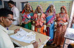 An official checks the names of Indian lambadi tribeswomen at a polling station during India's general election at Pedda Shapur village on the outskirts of Hyderabad on April 11, 2019. - India's mammoth six-week general election kicked off April 11, with polling stations in the country's northeast among the first to open. (Photo by NOAH SEELAM / AFP)