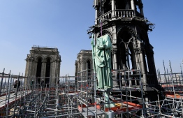 One of 16 copper statues, sitting 50 meters above the ground, is lifted off the Notre-Dame-de-Paris Cathedral to be taken for restoration on April 11, 2019 in the French capital Paris. - Using a 120 meter crane at the foot of the cathedral, the sixteen statues, the 12 apostles and the 4 evangelists, which sit around the spire of the cathedral are being removed to be sent to Perigueux, in southwest France for restoration. The absence of the statues will also signal the start of the renovation work of the spire that will last until 2022. Only then will the statues,  commisioned in the 1860s during the great restoration of the cathedral by Viollet-le-Duc, return to their original place. (Photo by BERTRAND GUAY / AFP)