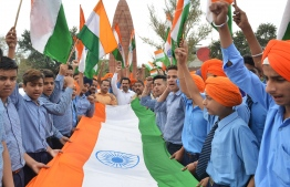 Indian school students hold Indian national flag as they pay tribute to the Jallianwala Bagh massacre martyrs' on the eve of the 100th anniversary of the Jallianwala Bagh massacre, in Amritsar on April 12, 2019. - The Amritsar massacre, also known as the Jallianwala Bagh massacre, took place on April 13, 1919, when British Indian Army soldiers on the direct orders of their British officers opened fire on an unarmed gathering killing at least 379 men, women and children, according to official records. (Photo by NARINDER NANU / AFP)