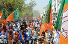 Indian Bharatiya Janta Party (BJP) supporters gather to follow BJP National President Amit Shah during his road show in Ahmedabad on April 6, 2019. - India is holding a general election to be held nearly six weeks starting on April 11, when hundreds of millions of voters will cast ballots in the world's biggest democracy. (Photo by SAM PANTHAKY / AFP)
