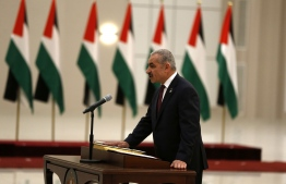 Mohammad Shtayyeh is sworn in as prime minister in the Israeli-occupied West Bank town of Ramallah, on April 13, 2019. - Shtayyeh announced his new cabinet today alongside president Mahmud Abbas. Several key positions were unchanged from the previous administration of Rami Hamdallah. (Photo by ABBAS MOMANI / AFP)