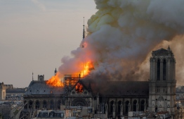 Smoke billows as flames burn through the roof of the Notre-Dame de Paris Cathedral on April 15, 2019, in the French capital Paris. - A huge fire swept through the roof of the famed Notre-Dame Cathedral in central Paris on April 15, 2019, sending flames and huge clouds of grey smoke billowing into the sky. The flames and smoke plumed from the spire and roof of the gothic cathedral, visited by millions of people a year. A spokesman for the cathedral told AFP that the wooden structure supporting the roof was being gutted by the blaze. (Photo by Fabien Barrau / AFP)