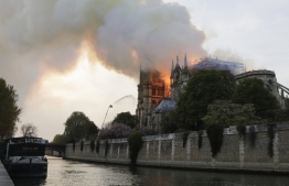 Flames and smoke are seen billowing from the roof at Notre-Dame Cathedral in Paris on April 15, 2019. - A fire broke out at the landmark Notre-Dame Cathedral in central Paris, potentially involving renovation works being carried out at the site, the fire service said. (Photo by Thomas SAMSON / AFP)