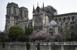 """Firefighters (below) work to extinguish a fire at Notre-Dame Cathedral in Paris early on April 16, 2019. - A huge fire that devastated Notre-Dame Cathedral is """"under control"""", the Paris fire brigade said early on April 16 after firefighters spent hours battling the flames. (Photo by STEPHANE DE SAKUTIN / AFP)"""
