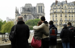People hug while looking at Notre-Dame-de-Paris on April 16, 2019 in the aftermath of a fire that devastated the cathedral. - Paris was struck in its very heart as flames devoured the roof of Notre-Dame, the medieval cathedral made famous by Victor Hugo, its two massive towers flanked with gargoyles instantly recognisable even by people who have never visited the city. (Photo by Bertrand GUAY / AFP)