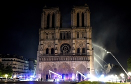 Fire fighter douse the Notre-Dame de Paris Cathedral after a fire broke out on April 15, 2019, in the French capital Paris. - A huge fire swept through the roof of the famed Notre-Dame Cathedral in central Paris on April 15, 2019, sending flames and huge clouds of grey smoke billowing into the sky. The flames and smoke plumed from the spire and roof of the gothic cathedral, visited by millions of people a year. A spokesman for the cathedral told AFP that the wooden structure supporting the roof was being gutted by the blaze. (Photo by STEPHANE DE SAKUTIN / AFP)