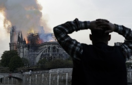 A man watches the landmark Notre-Dame Cathedral burn, engulfed in flames, in central Paris on April 15, 2019. - A huge fire swept through the roof of the famed Notre-Dame Cathedral in central Paris on April 15, 2019, sending flames and huge clouds of grey smoke billowing into the sky. The flames and smoke plumed from the spire and roof of the gothic cathedral, visited by millions of people a year. A spokesman for the cathedral told AFP that the wooden structure supporting the roof was being gutted by the blaze. (Photo by Geoffroy VAN DER HASSELT / AFP)