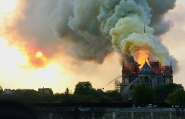 Flames and smoke are seen billowing from the roof at Notre-Dame Cathedral in Paris on April 15, 2019. - A fire broke out at the landmark Notre-Dame Cathedral in central Paris, potentially involving renovation works being carried out at the site, the fire service said.Images posted on social media showed flames and huge clouds of smoke billowing above the roof of the gothic cathedral, the most visited historic monument in Europe. (Photo by Fouad Maghrane / AFP)