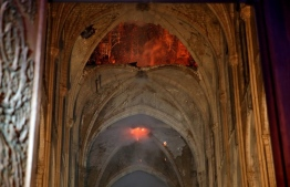 Flames and smoke are seen as the interior of the Notre-Dame Cathedral continues to burn on April 15, 2019, in the French capital Paris. - A huge fire swept through the roof of the famed Notre-Dame Cathedral in central Paris on April 15, 2019, sending flames and huge clouds of grey smoke billowing into the sky. The flames and smoke plumed from the spire and roof of the gothic cathedral, visited by millions of people a year. A spokesman for the cathedral told AFP that the wooden structure supporting the roof was being gutted by the blaze. (Photo by PHILIPPE WOJAZER / POOL / AFP)