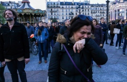 A woman cries as people look at Notre-Dame de Paris Cathedral engulfed in flames from the Paris's Hotel de Ville esplanade on April 15, 2019. - A huge fire swept through the roof of the famed Notre-Dame Cathedral in central Paris on April 15, 2019, sending flames and huge clouds of grey smoke billowing into the sky. The flames and smoke plumed from the spire and roof of the gothic cathedral, visited by millions of people a year. (Photo by STR / AFP)