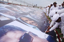 Pakistanis place flower on the images of the Christchurch Al Noor mosque victims to show their solidarity, in Jhang, in Pakistan's Punjab province on April 12, 2019. - Thousands of Pakistanis clad in white gathered in the central city of Jhang on April 12 to make a human image of Christchurch's Al Noor mosque, where 50 people were killed by a white supremacist four weeks ago. (Photo by MANSOOR ABBAS / AFP)