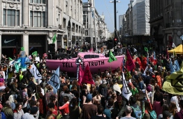"Environmental protesters from the Extinction Rebellion group gather around a pink boat as they take part in a demonstration at the junction of Oxford Street and Regent Street in London on April 15, 2019. - Environmental protesters from the Extinction Rebellion campaign group started a programme of demonstrations designed to block five of London's busiest and iconic locations to draw attention to what they see as the ""Ecological and Climate Emergency"" of climate change. (Photo by Daniel LEAL-OLIVAS / AFP)"