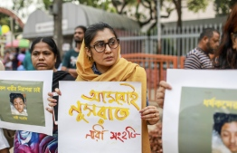 In this photo taken on April 12, 2019 Bangladeshi women hold placards and photographs of schoolgirl Nusrat Jahan Rafi at a protest in Dhaka, following her murder by being set on fire after she had reported a sexual assault. - A schoolgirl was burned to death in Bangladesh on the orders of her head teacher after she reported him for sexually harassing her, police said April 19. The death of 19-year-old Nusrat Jahan Rafi last week sparked protests across the South Asian nation, with the prime minister promising to prosecute all those involved. (Photo by SAZZAD HOSSAIN / AFP)