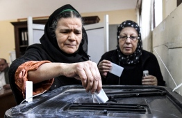 Elderly Egyptian women cast their ballots in a box as they vote at a polling station in a referendum on constitutional amendments, at a school in the capital Cairo's northern neighbourhood of Shubra, on the first day of a three-day poll, on April 20, 2019. Polls in Egypt opened on April 20 for 62 million eligible voters to make their voice hear on a referendum that could keep President Abdel Fattah al-Sisi in power until 2030. On the ballot is a raft of constitutional changes that would extend Sisi's current term by two years. He would be eligible to run for six more years in 2024. PHOTO/AFP
