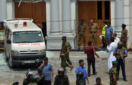 An ambulance is seen outside the church premises with gathered people and security personnel following a blast at the St. Anthony's Shrine in Kochchikade, Colombo on April 21, 2019. - At least 42 people were killed April 21 in a string of blasts at hotels and churches as worshippers attended Easter services, a police official told AFP. (Photo by ISHARA S. KODIKARA / AFP)