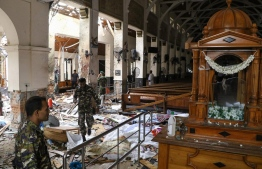 Sri Lankan security personnel walk past dead bodies covered with blankets amid blast debris at St. Anthony's Shrine following an explosion in the church in Kochchikade in Colombo on April 21, 2019. A string of blasts ripped through high-end hotels and churches holding Easter services in Sri Lanka on April 21, killing at least 156 people, including 35 foreigners. ISHARA S. KODIKARA / AFP