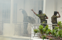 Sri Lankan Special Task Force (STF) personnel gesture outside a house during a raid -- after a suicide blast had killed police searching the property -- in the Orugodawatta area of the capital Colombo on April 21, 2019, following a series of blasts in churches and hotels. - A string of blasts ripped through high-end hotels and churches holding Easter services in Sri Lanka on April 21, killing at least 156 people, including 35 foreigners. (Photo by ISHARA S. KODIKARA / AFP)