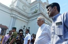 Sri Lankan Prime Minister Ranil Wickremasinghe (2nd R) arrives to visit the site of a bomb attack at St. Anthony's Shrine in Kochchikade in Colombo on April 21, 2019. - A string of blasts ripped through high-end hotels and churches holding Easter services in Sri Lanka on April 21, killing at least 156 people, including 35 foreigners. (Photo by ISHARA S. KODIKARA / AFP)