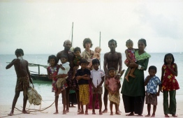 Gayle and Dhonkokko pictures with islanders on the beach. PHOTO: FRANK BURNABY