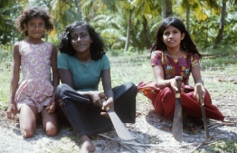 Maldivian girls pictured with kathi valhi (a strong knife used in everyday activities such as collecting firewood). PHOTO: FRANK BURNABY