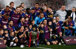 Barcelona's players celebrate with the Liga trophy after winning the club's 26th league title at the end of the Spanish League football match between Barcelona and Levante at the Camp Nou stadium in Barcelona on April 27, 2019. (Photo by PAU BARRENA / AFP)
