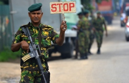 A Sri Lankan Special Task Force (STF) soldier stops a vehicle in Colombo on April 27, 2019, following a series of bomb blasts targeting churches and luxury hotels on Easter Sunday in Sri Lanka. - Fifteen people including six children have died during a Sri Lankan security forces operation in the aftermath of the Easter attacks, as three cornered suicide bombers blew themselves up and others were shot dead, police said on April 27. (Photo by ISHARA S.  KODIKARA / AFP)
