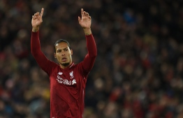 Liverpool's Dutch defender Virgil van Dijk acknowledges supporters  during the English Premier League football match between Liverpool and Huddersfield at Anfield in Liverpool, north west England on April 26, 2019. (Photo by Oli SCARFF / AFP) / RESTRICTED TO EDITORIAL USE. No use with unauthorized audio, video, data, fixture lists, club/league logos or 'live' services. Online in-match use limited to 120 images. An additional 40 images may be used in extra time. No video emulation. Social media in-match use limited to 120 images. An additional 40 images may be used in extra time. No use in betting publications, games or single club/league/player publications. /