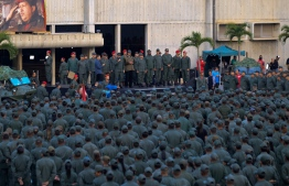 """This handout picture released by Miraflores Palace press office shows Venezuela's President Nicolas Maduro (C) delivering a message to loyal troops at the """"Fuerte Tiuna"""" in Caracas, Venezuela on May 2, 2019. - Maduro attends a """"march to reaffirm the absolute loyalty"""" of the Venezuelan Army, as opposition leader Juan Guaido continues making calls to oust his government. (Photo by HO / Presidency/JHONN ZERPA / AFP)"""