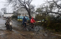 Indian residents ride along a road next to damaged trees oafter Cyclone Fani landfall in Puri in the eastern Indian state of Odisha on May 3, 2019. - Two people died on May 3 after Cyclone Fani slammed into eastern India, officials said, as the storm sent coconut trees flying, blew away food stands and cut off power and water. The monster weather system, which made landfall at the eastern holy city of Puri in the morning, is one of the strongest to come in off the Indian Ocean in years, with winds gusting at speeds of up to 200 kilometres (125 miles) per hour. (Photo by Dibyangshu SARKAR / AFP)