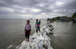 Bangladeshi children walk over the top of a sandbag embankment that was breached by high waters in Khulna on May 4, 2019, as Cyclone Fani reached Bangladesh. - Cyclone Fani, one of the biggest to hit India in years, barrelled into Bangladesh on May 4 after leaving a trail of deadly destruction in India. (Photo by MUNIR UZ ZAMAN / AFP)