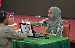 An official at Ministry of Islamic Affairs collecting fitr zakat payments on Tuesday. PHOTO; HUSSAIN WAHEED / MIHAARU