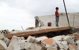 A Syrian boy stands above the rubble of a building in the village of Rabaa Jour in the the jihadist-held Syrian province of Idlib on May 6, 2019 following reported shelling and air strikes in the area. - Clashes between Syrian regime forces and jihadists killed more than 26 fighters in the country's northwest, which has seen an escalation in shelling and air strikes, a monitor said. (Photo by OMAR HAJ KADOUR / AFP)