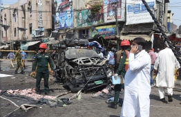 Pakistani security officials examine the site of a bomb blast outside a Sufi shrine in Lahore on May 8, 2019. - A blast at one of Pakistan's oldest and most popular Sufi shrines killed at least five people and wounded 24 in the eastern city of Lahore May 8, police said, as the country marks the fasting month of Ramadan. (Photo by ARIF ALI / AFP)