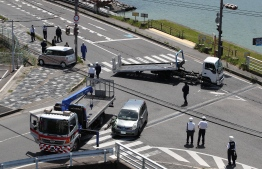 Police officers remove vehicles that ploughed into a group of kindergarten children leaving at least four of them critically injured at a crossing in Otsu, Shiga prefecture on May 8, 2019. - JAPAN OUT (Photo by JIJI PRESS / JIJI PRESS / AFP) /