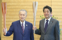 Japanese Prime Minister Shinzo Abe (R) and Tokyo 2020 Olympic and Paralympic games organising committee president Yoshiro Mori (L) pose while holding Olympic torches at Abe's official residence in Tokyo on May 9, 2019. - JAPAN OUT (Photo by JIJI PRESS / JIJI PRESS / AFP) /