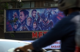"""(FILES) In this file photo taken on April 25, 2019, Indian vehicles go past a movie theatre displaying a poster of the latest Avengers movie, in Mumbai. - """"Avengers: Endgame"""" led the North American box office for a third week running, but the cuddly creatures of a new """"Pokemon"""" movie gave the superheroes a run for its money, industry watchers said on May 12, 2019. (Photo by Indranil MUKHERJEE / AFP)"""