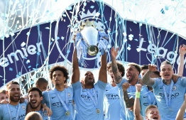 Manchester City's Belgian defender Vincent Kompany (C) holds up the Premier League trophy after their 4-1 victory in the English Premier League football match between Brighton and Hove Albion and Manchester City at the American Express Community Stadium in Brighton, southern England on May 12, 2019. - Manchester City held off a titanic challenge from Liverpool to become the first side in a decade to retain the Premier League on Sunday by coming from behind to beat Brighton 4-1 on Sunday. (Photo by Glyn KIRK / AFP) / RESTRICTED TO EDITORIAL USE. No use with unauthorized audio, video, data, fixture lists, club/league logos or 'live' services. Online in-match use limited to 120 images. An additional 40 images may be used in extra time. No video emulation. Social media in-match use limited to 120 images. An additional 40 images may be used in extra time. No use in betting publications, games or single club/league/player publications. /