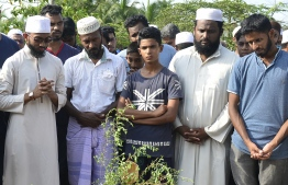Relatives mourn beside the coffin of Fauzul Ameen, the victim of an anti-Muslim riots, during a burial ceremony in a Muslim cemetery in Nattandiya on May 14, 2019. - Sri Lanka's police declared on May 14 a nationwide curfew for a second night running, after anti-Muslim riots killed one man and left dozens of shops, homes and mosques damaged. PHOTO: LAKRUWAN WANNIARACHCHI / AFP